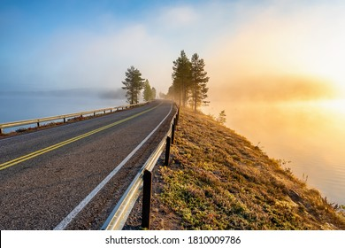Finnish landscape with narrow car road through the lake. Foggy early morning in autumn at sunrise in Finland