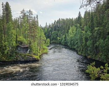 Finnish landscape with an old fisherman's hut along the Oulankajoki river at the Oulanka National Park in Kuusamo, Finland. Scenic view of the northern nature and the flowing water in the stream.