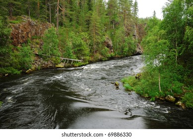 Finnish rapid river is running in the middle of the taiga forest.