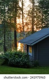 Finnish sauna cottage in luminous midsummer night lakeside