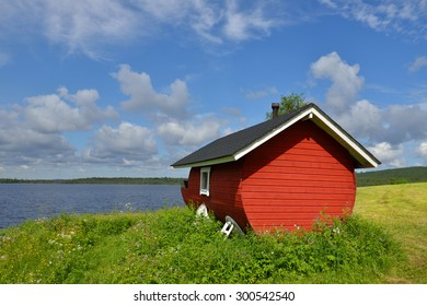 Finnish sauna on the shore of the blue lake summer day. Northern Finland, Lapland