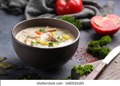 Finnish soup with salmon, potatoes, carrots, tomatoes and cream in a deep grey bowl. Parsley, tomatoes, knife, spices  and salt on a grey background. Top view. Background image, copy space