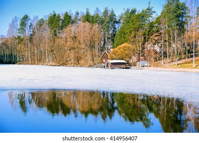 Finnish spring landscape with lake, forest and cottage