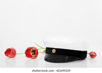 finnish student cap, ylioppilaslakki with tree red tulips and white background
