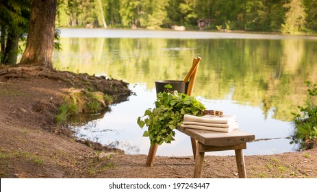 Finnish summer landscape and sauna objects on wooden bench by lake. Midsummer view from Finland.