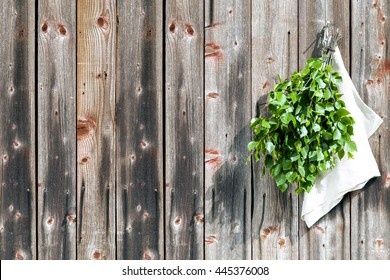 finnish traditional summery sauna accessory vihta or vasta made of silver birch branches hanging on old wood panel wall with towel