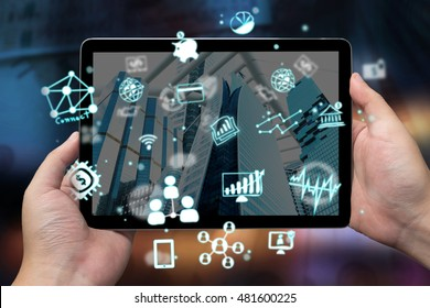 Fintech concept , Financial and technology concept .Man hand holding tablet with icons on screen and abstract background