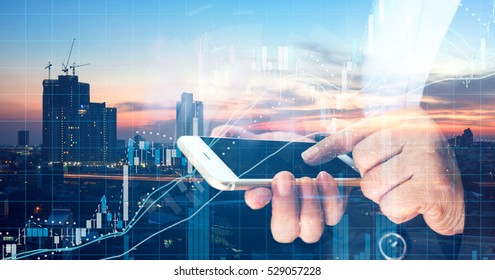 Fintech ,Forex and stock market concept. Business woman point finger to screen mobile phone and technical chart with metropolis city sunset background