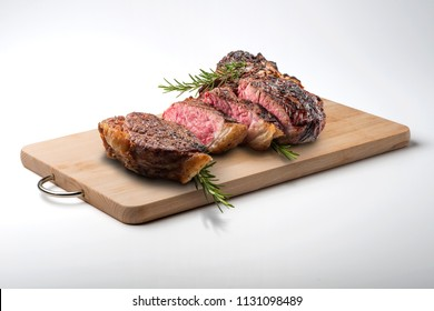 Fiorentina T-bone steak cut on rectangular wooden chopping board isolated on white background