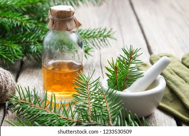 Fir aromatic oil. Pine essential oil in a glass bottle. Coniferous tree branches, gloves and mortar.