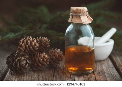 Fir aromatic oil. Pine essential oil in a glass bottle, spruce cones, coniferous tree branches and mortar.