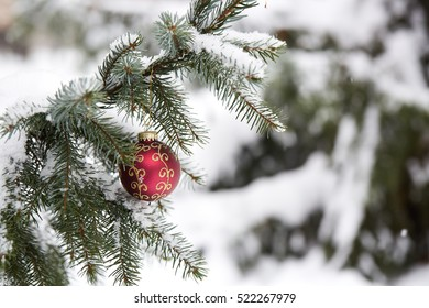 Fir branch with christmas toys and snow. Outdoors. New Year and Christmas background.