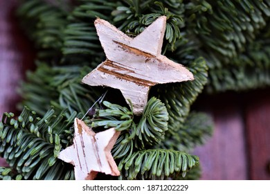 Fir branch christmasdecoration with two small stars of birch as a close up