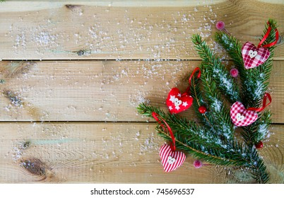 fir branches with cloth hearts on wood