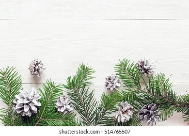Fir branches with cones on a white painted wooden boards. Christmas background. Space for text. Top view.