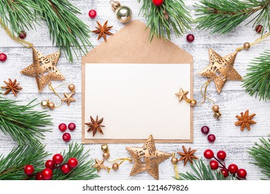 Fir branches, gifts and an envelope on a light wooden background. Cranberries, spices, holly berries. Christmas background. Flat lay, top view, copy space.