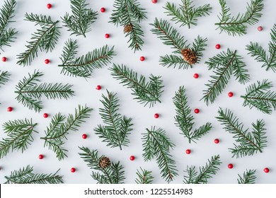 Fir branches with red berries background pattern. Winter flat lay composition. Top view.