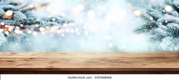 Fir branches in snow with wooden table and festive bokeh at christmas time