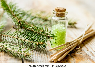 fir branches and spruce bath salt on wooden table background