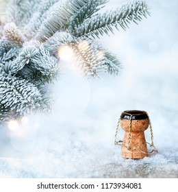 Fir branches in winter with champagne cork in the snow and bokeh for a new year