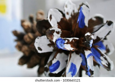 The fir cone is painted with white and blue dyes