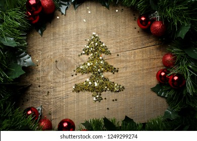 Fir of gold glitter on wooden background. Fir branches on a wooden background, decoration. Christmas and New Year. spruce gold spangles. top view. Cristmas card.