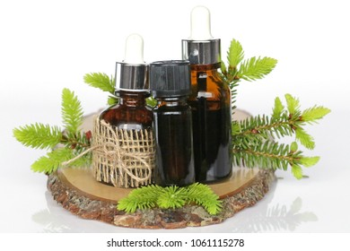 Fir Needle Essential Oil set. essential oil spruce. spruce oil bottles set in brown glass bottles with a pipette and sprigs of spruce on a piece of wood . aroma pine oil.