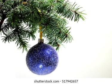 Fir tree branch isolated on white background with gold thread and a pin holds a blue ball in top frame corner. New Year and Christmas blank template. Big white copyspace place for text.
