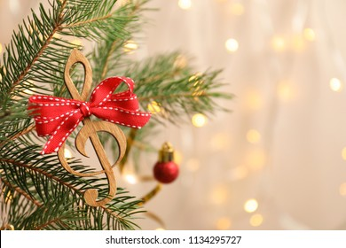 Fir tree branch with wooden treble clef on blurred background. Christmas music concept