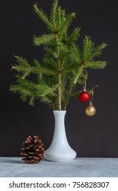 Fir tree branches with christmas balls in a vase. Still life.