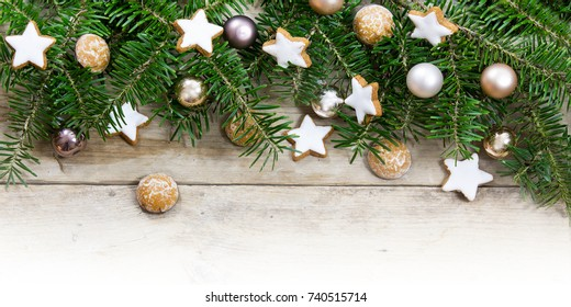 Fir tree branches decorated with golden christmas balls and cookies as a border on bright rustic wood, holiday background frame with copy space, panorama format