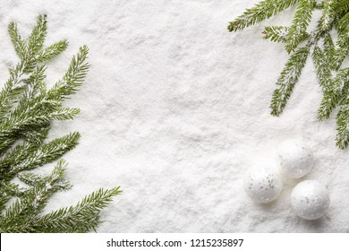 Fir tree branches with decorations and gift box on a snow background with copy space. Top view. Christmas and New Year. Winter holiday. Greeting card