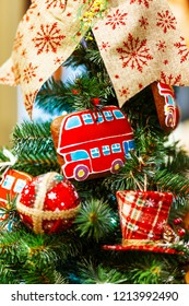 Fir tree decorated with gingerbread in shape of double decker bus and fabric balls for Christmas and New Year celebration.