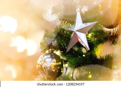 Fir tree decorated with shiny balls, star and light bulbs for Christmas and New Year celebration.