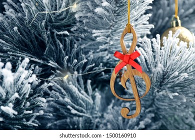 Fir tree with wooden treble clef and decor, closeup view. Christmas music