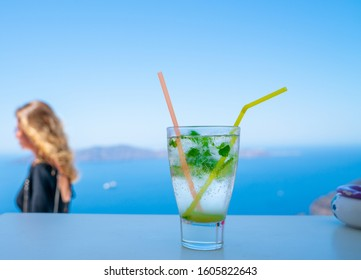 Fira, Santorini - August 8 2019; Cool frosty glass with mojito drink in focus in foreground with person in background out of focus.