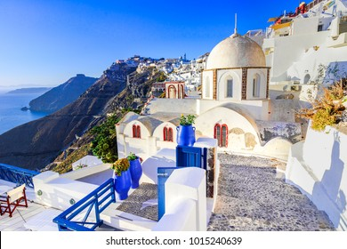 Fira, Santorini - Greek Islands landmark with white village, cobbled paths, greek orthodox blue church and sunset over caldera. Cyclades, Greece