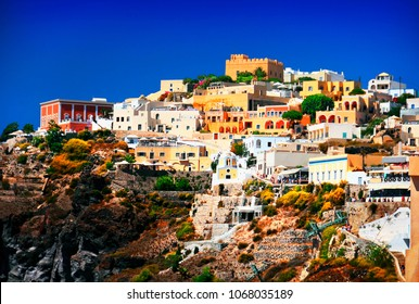 Fira (Thira), Santorini island, Cyclades, Southern Greece. Beautiful greek city scenery, traditional cycladic and venetian architecture at the top of black volcanic rocks against blue sky at evening