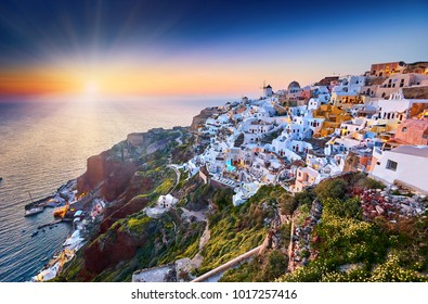 Fira town on Santorini island, Greece. Incredibly romantic sunset on Santorini. Oia village with mills in the evening light. Amazing sunset view with white houses. Island of lovers