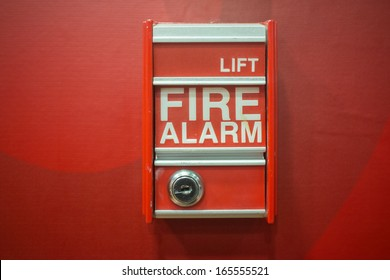 Fire alarm box on modern red wall