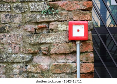 Fire alarm box on white cement wall for security warning alert, push button fire alarm in the building, isolated fire alarm botton box.