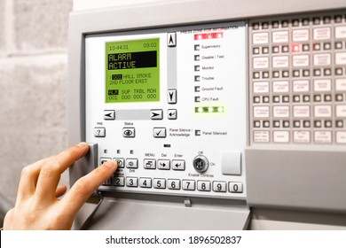 Fire alarm control panel is activated and in alert mode. Display message: Alarm active hall smoke. Red flickering lights and peeping. A hand is using the silence button. Selective focus.