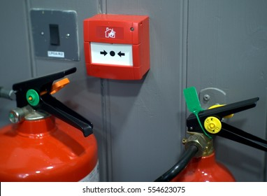 fire alarm equipment on wooden grey wall and two fire extinguisher and security system button