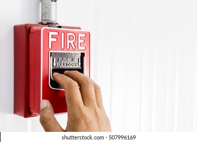 Fire alarm switch, The hand of man is pulling fire alarm on the wall next to the door,Fire alarm switch.Break glass and press button to activate. With hand and direction arrow, Hand push fire botton.