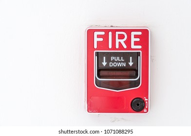 Fire alarm switch on white wall background.