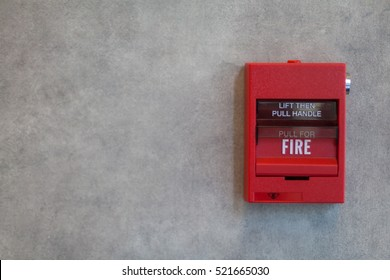 Fire alarm system in red color on grey wall.
