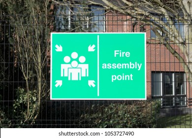 Fire assembly point sign post at workplace for health safety of employees and people from emergency escape