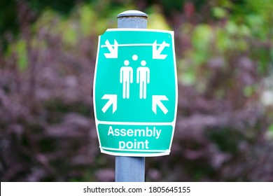 Fire assembly point sign at workplace signpost