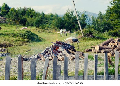 Fire in backyard and man out of focus preparing lamb meat for cooking on a spit. Selective focus
