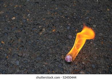 Fire ball burning on a black asphalt cement